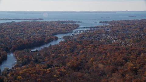AX119_229.0000100F - Aerial stock photo of Small town community and bridges over Mianus River in Autumn, Greenwich, Connecticut