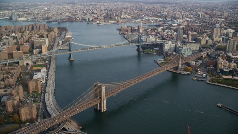 AX120_128.0000261F - Aerial stock photo of Manhattan and Brooklyn Bridges spanning the East River in New York City