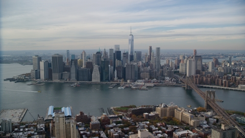 AX120_134.0000082F - Aerial stock photo of Lower Manhattan, the East River, and the Brooklyn Bridge in Autumn, New York City