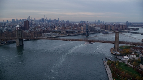 AX121_023.0000020F - Aerial stock photo of The Brooklyn and Manhattan Bridges at sunset in New York City