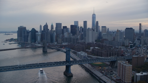 AX121_029.0000120F - Aerial stock photo of The Brooklyn Bridge, Manhattan Bridge, and Lower Manhattan at sunset in New York City