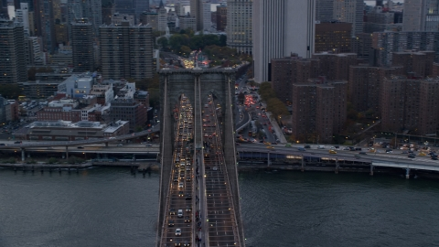 AX121_040.0000074F - Aerial stock photo of Heavy traffic on the Brooklyn Bridge at sunset in New York City