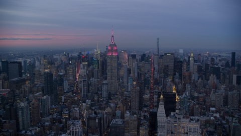 AX121_081.0000239F - Aerial stock photo of Empire State Building with pink lights and Midtown high-rises at Sunset in New York City