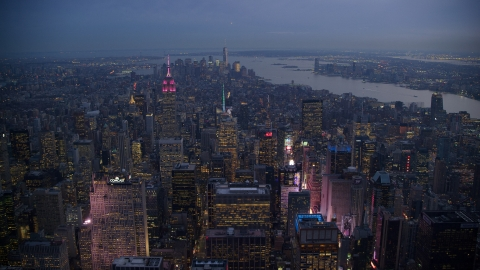 AX121_103.0000219F - Aerial stock photo of Times Square and Midtown skyscrapers with Lower Manhattan in the background at sunset, New York City