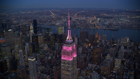 AX121_108.0000414F - Aerial stock photo of The Empire State Building with pink lights at sunset in Midtown, New York City
