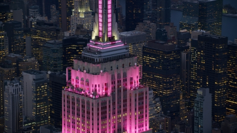 AX121_109.0000095F - Aerial stock photo of Empire State Building with pink lighting at sunset in Midtown Manhattan, New York City