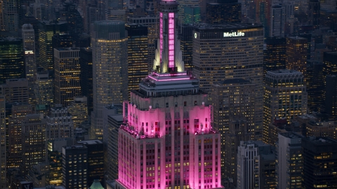 AX121_109.0000359F - Aerial stock photo of Pink lights on the Empire State Building at sunset in Midtown Manhattan, New York City