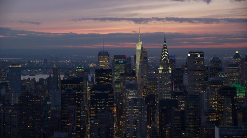 AX121_116.0000116F - Aerial stock photo of The Chrysler Building and Midtown Manhattan skyscrapers at sunset in New York City