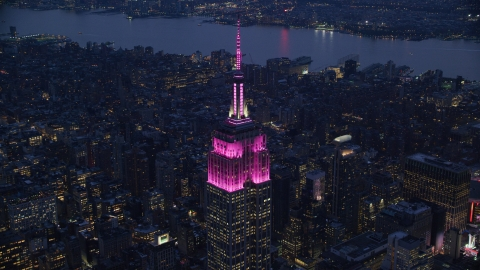 AX121_127.0000132F - Aerial stock photo of The Empire State Building with pink lights at sunset in Midtown, New York City