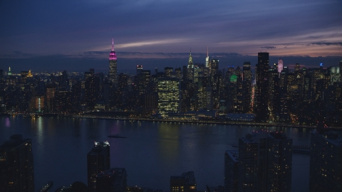 AX121_144.0000032F - Aerial stock photo of Midtown Manhattan across the East River at night in New York City