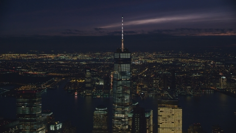 AX121_161.0000259F - Aerial stock photo of Freedom Tower rising above Lower Manhattan at night in New York City
