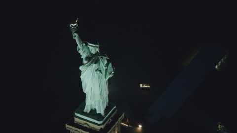 AX121_168.0000211F - Aerial stock photo of Statue of Liberty at nighttime in New York