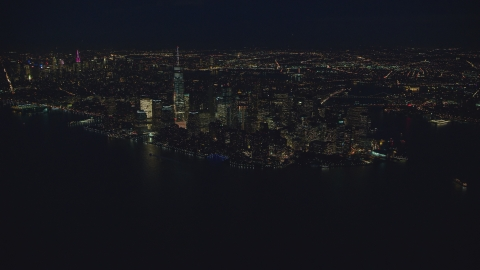 AX121_171.0000102F - Aerial stock photo of Lower Manhattan at night, New York City, seen from New York Harbor