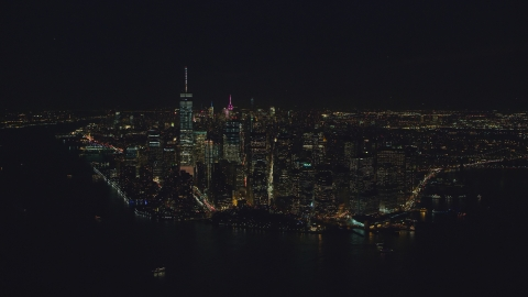 AX121_194.0000066F - Aerial stock photo of Lower Manhattan at night, seen from New York Harbor in New York City