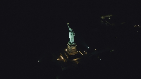 AX121_195.0000063F - Aerial stock photo of The Statue of Liberty at night, New York