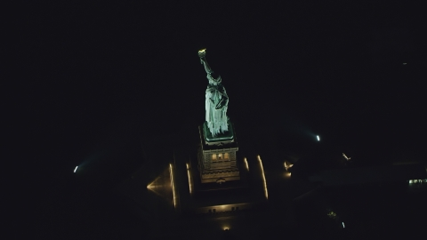 AX121_195.0000229F - Aerial stock photo of The side of the Statue of Liberty at night in New York
