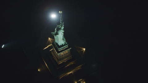 AX121_196.0000108F - Aerial stock photo of A bird's eye view of the back of the Statue of Liberty at night in New York