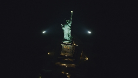 AX121_196.0000217F - Aerial stock photo of A bird's eye of the Statue of Liberty at nighttime in New York
