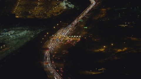 AX121_199.0000070F - Aerial stock photo of Heavy traffic at a Jersey City toll station at night, New Jersey