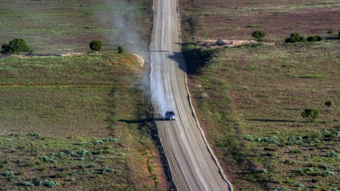 AX138_223.0000047 - Aerial stock photo of Silver SUV trailing a plume of dust on Hatch Point Road, Moab, Utah