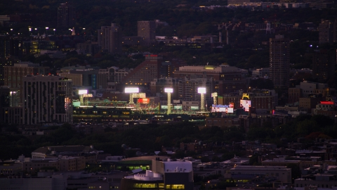 AX141_014.0000174 - Aerial stock photo of Bright lights and a baseball game at Fenway Park, Boston, Massachusetts, twilight