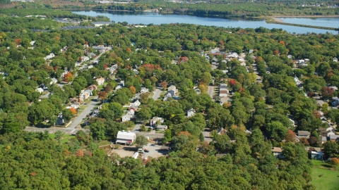 AX143_004.0000035 - Aerial stock photo of Small town neighborhoods and trees in autumn, Randolph, Massachusetts