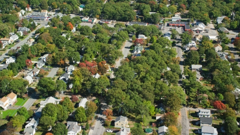 AX143_005.0000000 - Aerial stock photo of Small town neighborhood, trees in autumn, Randolph, Massachusetts