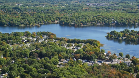 AX143_014.0000107 - Aerial stock photo of A small town by Whitmans Pond in autumn, Weymouth, Massachusetts