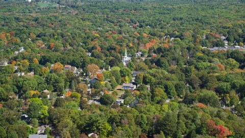 AX143_017.0000354 - Aerial stock photo of A small town with autumn trees around a church, Hingham, Massachusetts