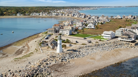 AX143_040.0000335 - Aerial stock photo of Old Scituate Light, beach, and oceanfront homes, Scituate, Massachusetts