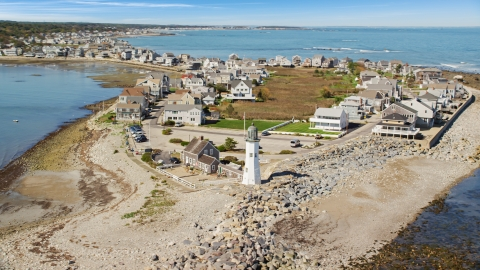 AX143_041.0000204 - Aerial stock photo of A beach, oceanfront homes, and Old Scituate Light, Scituate, Massachusetts