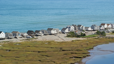 AX143_049.0000000 - Aerial stock photo of A row of elevated oceanfront homes, Humarock, Massachusetts