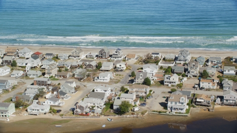AX143_053.0000266 - Aerial stock photo of A group of oceanfront homes near ocean waves crashing, Humarock, Massachusetts