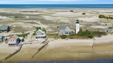 AX143_144.0000125 - Aerial stock photo of Sandy Neck Colony houses by Sandy Neck Light on Cape Cod, Barnstable, Massachusetts