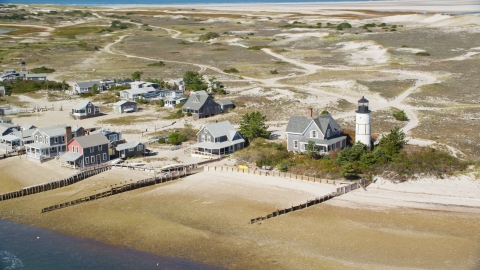 AX143_145.0000000 - Aerial stock photo of Sandy Neck Colony homes beside Sandy Neck Light, Cape Cod, Barnstable, Massachusetts