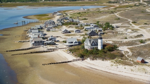 AX143_145.0000207 - Aerial stock photo of Beachfront houses at Sandy Neck Colony by Sandy Neck Light, Cape Cod, Barnstable, Massachusetts