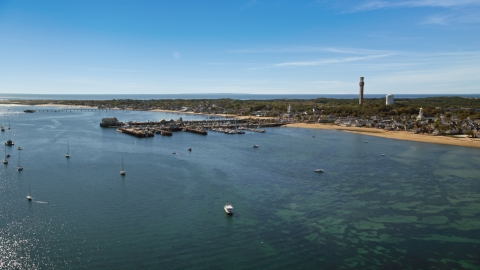 AX143_221.0000256 - Aerial stock photo of Piers by a small coastal town, Provincetown, Massachusetts