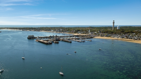 AX143_222.0000000 - Aerial stock photo of Boats docked at piers beside a small coastal town, Provincetown, Massachusetts