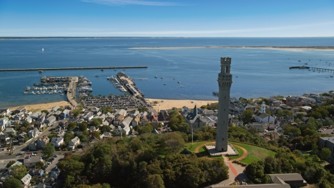 AX143_228.0000285 - Aerial stock photo of The Pilgrim Monument and small coastal town with a view of piers and the bay, Provincetown, Massachusetts
