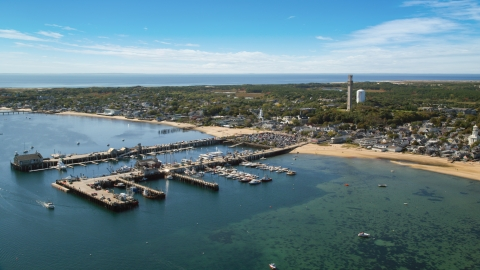 AX143_231.0000282 - Aerial stock photo of A small coastal town seen from near piers in the bay, Provincetown, Massachusetts