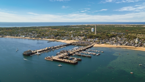 AX143_232.0000117 - Aerial stock photo of Piers and a small coastal town seen from the bay, Provincetown, Massachusetts