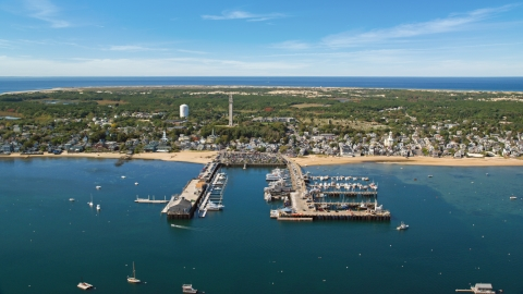 AX143_233.0000122 - Aerial stock photo of Boats docked at piers by a small coastal town, Cape Cod, Provincetown, Massachusetts