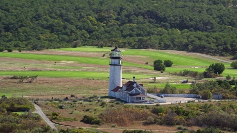 AX144_015.0000127 - Aerial stock photo of Highland Light near dense forest, Cape Cod, Truro, Massachusetts