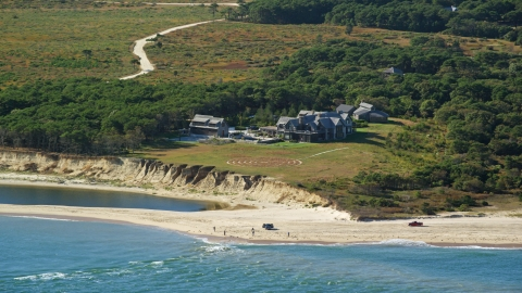AX144_124.0000000 - Aerial stock photo of An isolated beachfront mansion and trucks on the beach, Chappaquiddick Island, Martha's Vineyard, Massachusetts