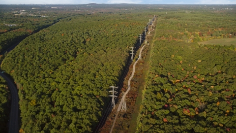 AX145_125.0000000 - Aerial stock photo of Power lines through deciduous forest in autumn, Walpole, Massachusetts