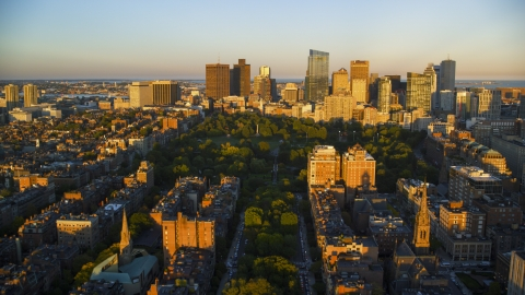 AX146_064.0000094F - Aerial stock photo of Historic Boston Common and skyscrapers in Downtown Boston, Massachusetts, sunset