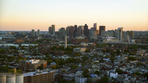 AX146_094.0000191F - Aerial stock photo of The Bunker Hill Monument and the Downtown Boston skyline, Charlestown, Massachusetts, sunset