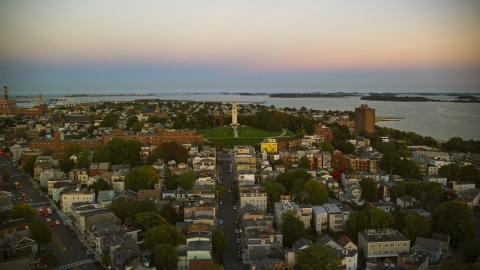 AX146_116.0000187F - Aerial stock photo of A view of of Dorchester Heights Monument and row houses in South Boston, Massachusetts, twilight