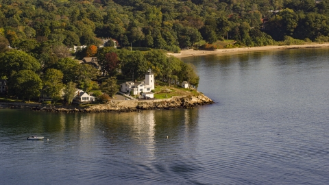 AX147_053.0000000 - Aerial stock photo of A lighthouse nestled among trees by cove, autumn, Beverly, Massachusetts