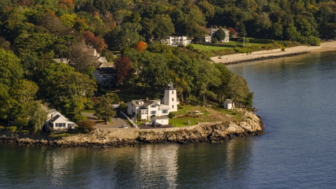 AX147_053.0000174 - Aerial stock photo of Hospital Point Light beside a cove, autumn, Beverly, Massachusetts